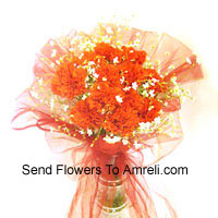 12 Orange Carnations With Some Ferns In A Vase