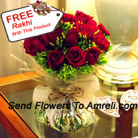 12 Red Roses With Some Ferns In A Vase And A Free Rakhi