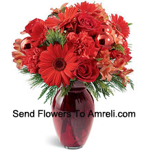 productA beautiful holiday red glass vase holds an array of crimson blossoms. Carnations, roses, Gerbera daisies and alstroemeria are decorated with shiny red glass ornaments and interspersed with Christmas greens. Great to give, or to keep for yourself!� (Please Note That We Reserve The Right To Substitute Any Product With A Suitable Product Of Equal Value In Case Of Non-Availability Of A Certain Product)