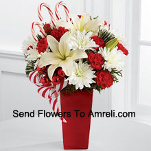 productBursts with the bright cheer and jubilant beauty of this special season. White Asiatic Lilies and chrysanthemums sit amongst red mini carnations, assorted holiday greens, red glass balls, three candy canes and festive ribbon, perfectly arranged in a red ceramic vase to create a lively bouquet of merry wishes for a splendid holiday season! (Please Note That We Reserve The Right To Substitute Any Product With A Suitable Product Of Equal Value In Case Of Non-Availability Of A Certain Product)