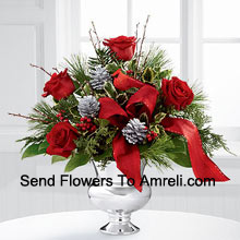 Highly elegant and bursting with your merriest wishes, this bouquet will create the perfect holiday gift. Rich red roses are vibrant and bright arranged with variegated holly, assorted holiday greens, silver pinecones and branches, all perfectly accented with a faux cardinal and designer red ribbon. Presented in a silver pedestal vase, this bouquet will add to the joy and festivities of their holiday season with each gorgeous bloom. (Please Note That We Reserve The Right To Substitute Any Product With A Suitable Product Of Equal Value In Case Of Non-Availability Of A Certain Product)