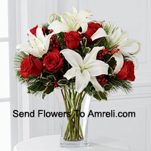 Fulfill their dreams for a glimpse of the season's inspired beauty. Rich red roses dazzle and delight when arranged with snowy white Oriental lilies accented with assorted holiday greens and variegated holly stems in a clear, sculpted glass vase. This bouquet offers them a warm wish for a lovely holiday season they will always hold dear. (Please Note That We Reserve The Right To Substitute Any Product With A Suitable Product Of Equal Value In Case Of Non-Availability Of A Certain Product)