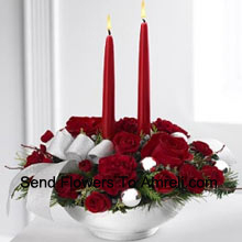 Our Holiday Elegance Centerpiece will add that special spark to their seasonal celebration with its vibrant array of crimson blooms! Red roses, carnations and sit amongst holiday greens in a Basket adorned with a beautiful silver ribbon accent and two taper candles to bring a holiday glow of warmth and peace to their table. (Please Note That We Reserve The Right To Substitute Any Product With A Suitable Product Of Equal Value In Case Of Non-Availability Of A Certain Product)
