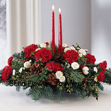 Share the joy this season with a festive fresh arrangement of red carnations and white pompons, winter greens and pinecones. Two red taper candles add seasonal charm to this centerpiece. (Please Note That We Reserve The Right To Substitute Any Product With A Suitable Product Of Equal Value In Case Of Non-Availability Of A Certain Product)