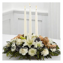 Celebrates the holiday season with winter grace and style. White lilies, carnations and roses create an exquisite display. Surrounding three white taper candles, this holiday centerpiece will add light and love to their seasonal celebration. (Please Note That We Reserve The Right To Substitute Any Product With A Suitable Product Of Equal Value In Case Of Non-Availability Of A Certain Product)